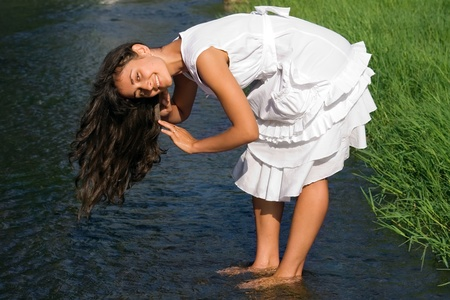 Pretty girl in white dress washing her hair in the river