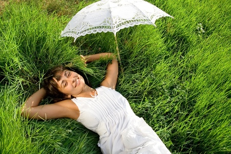 liying: Young pretty lady in white dress and with umblella having a rest on the green meadow