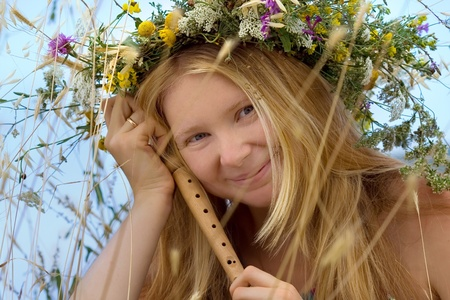 Portrait of a young smiling blond girl in herbal wreath with flute photo