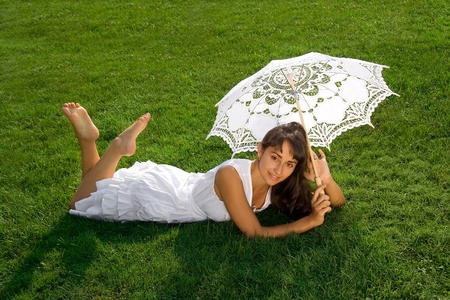 Smiling young pretty girl  in white with umbrella on the lawn