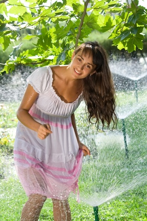 Pretty laughing  girl having fun on the lawn amoung the sprinklers photo