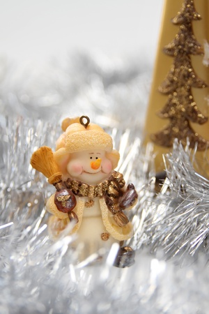 Christmas background with cheerful toy snowman and silver Christmas tinsel photo