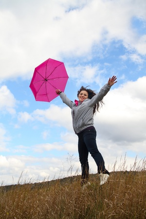 Joyful young lady jumping with bright pink umbrella on sky background Stock Photo