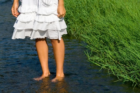 Pretty womans legs  cooling in the fresh stream near the green grass