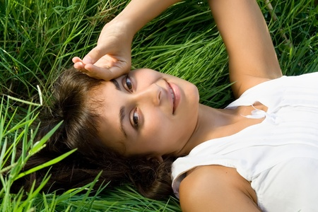 liying: Young attractive girl liying on the grass Stock Photo
