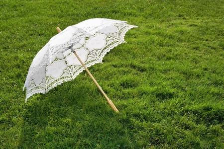 Beautiful white wedding umbrella on the green lawn