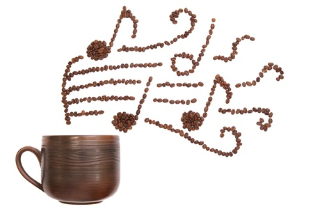 Composition with cup and coffee beans forming musical  notes photo