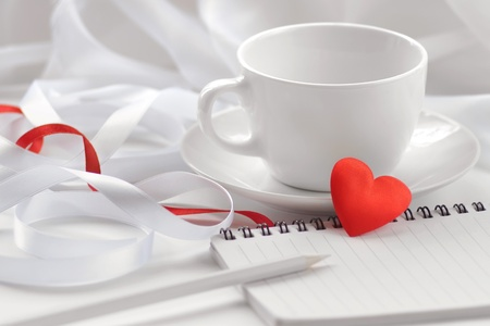 valentine day cup of coffee: White tea cup with note-pad, pencil and red heart.  Soft focus  Stock Photo