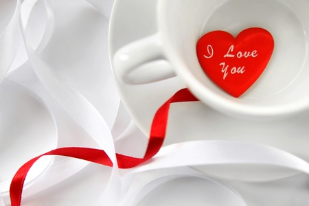 White ribbons and cup with red heart. Soft focus photo