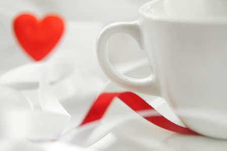 Romantic background with white cup and defocused red heart. Soft focus photo