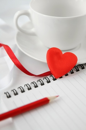 White tea cup with note-pad, pencil and red heart.  Soft focus  photo