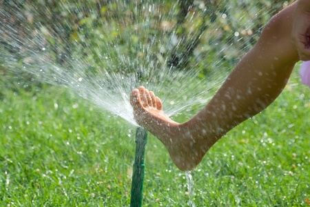 Female leg with the sprinkler on the green lawn