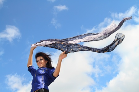Beautiful smiling  girl with scarfs fluttering on the wind
