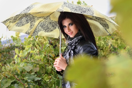 Stylish young girl with green umbrella in vineyard