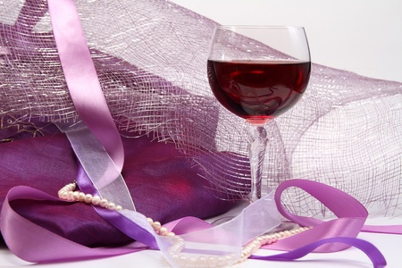 Glass with red wine on luxury background with beads and ribbons