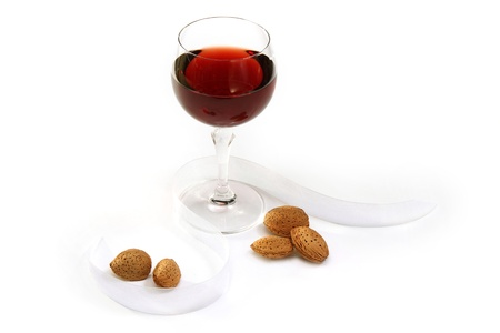 Glass of red wine and almonds on white background
