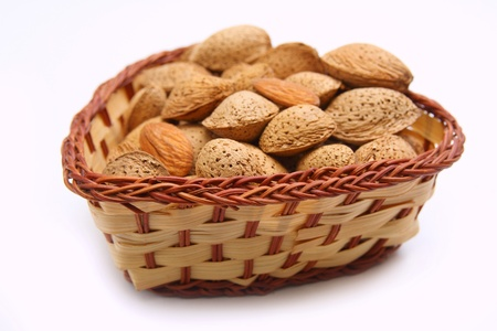 Fresh tasty almond nuts in wicker bowl isolated on white