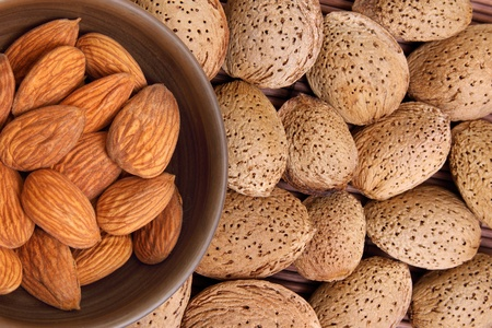Almond kernels in clay bowl with background of  shelled almonds Stock Photo