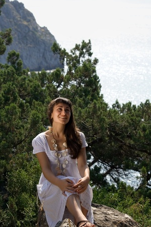 Young girl in white dress sitting on the rock  on the nature background