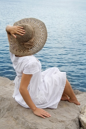 Young girl in the bonnet looking at the sea