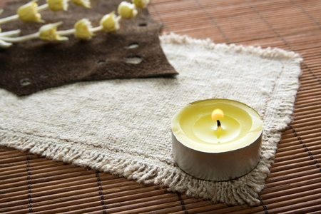 flaming yellow candle with herbs on textured background