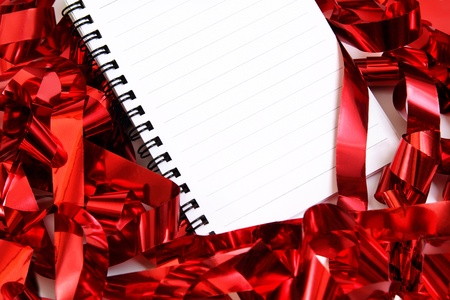Party background with writing-pad and red decorative ribbons photo