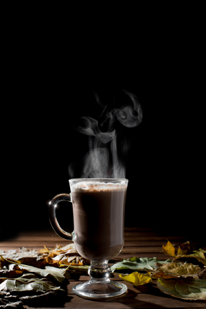 Cup of hot drink with steam over black background.