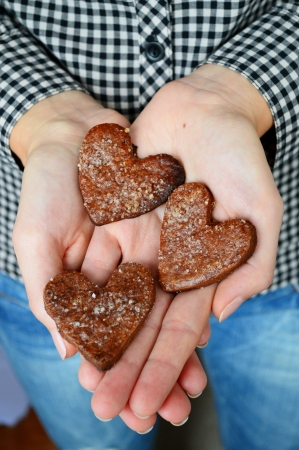 Chocolate chip cookies in the shape of hearts held in his hands. chocolate chip cookies with sugar photo