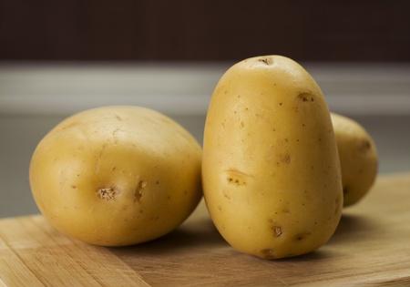 group of potatoes on breadboard indoor