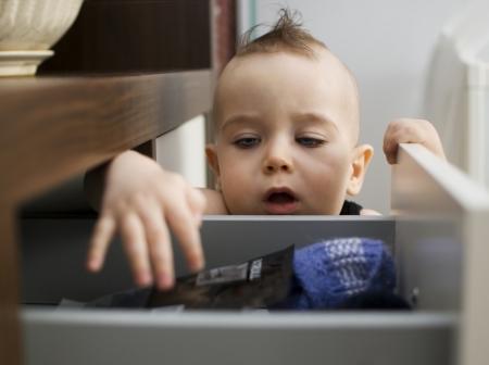 cajones: beb� curioso buscando algo en el caj�n Foto de archivo
