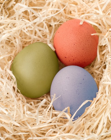 three easter colour eggs in nest