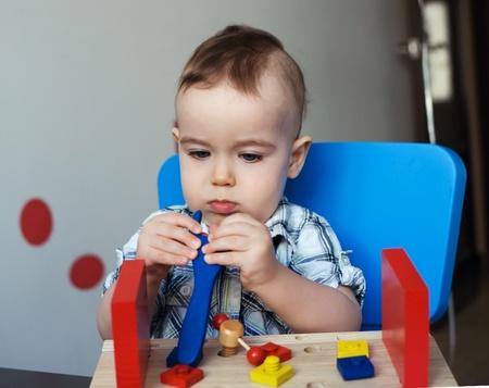 Petit gar�on jouant avec des jouets en bois