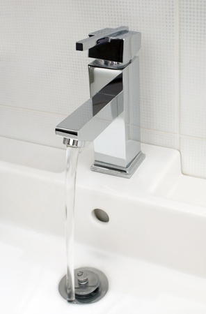 Closeup of modern bathroom tap, flowing tap water Standard-Bild