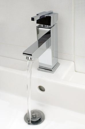 guarniciones: Detalle de grifo de ba�o moderno, que fluye agua del grifo