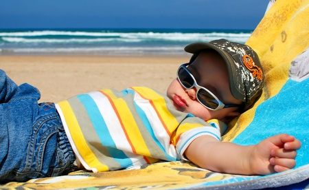 Portrait of one year old boy sleeping on beach Standard-Bild