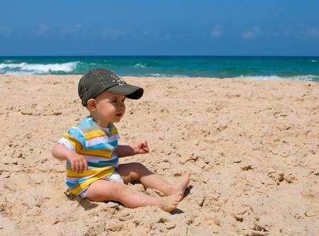 One year old boy sitting on sand