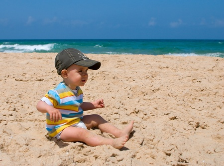 One year old boy sitting on sand  photo