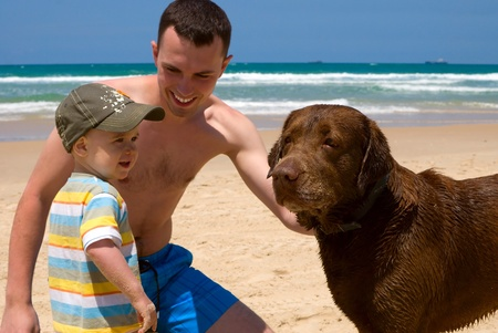 Happy father and son playing on beach with dog Stock Photo