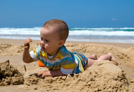 One year old boy lying down playing with sand