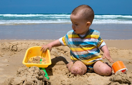 One year old child building sand castle on the beach