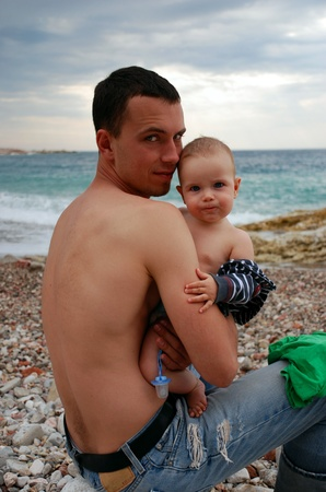 Father and son sitting near sea