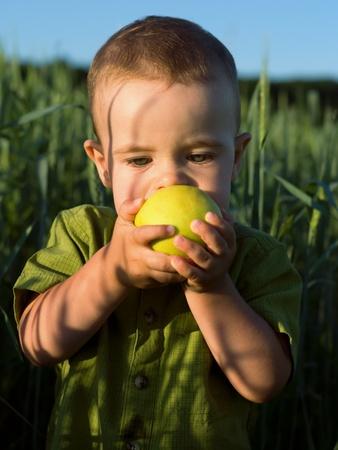 Portrait de petit gar�on mordre la pomme verte Banque d'images