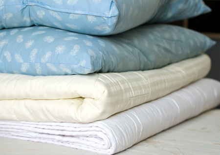 bed linen: Folded in a pile of blankets and feather pillows