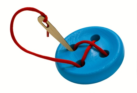 Button with needle for training fine motor skills