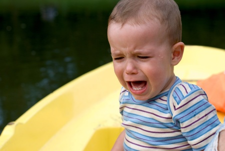 Crying boy in the yellow boat