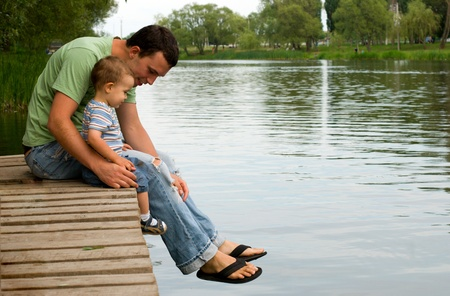 young boy smiling: Father and son sitting near a river