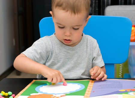 Boy play with color plasticine