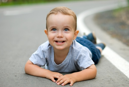 Happy child lying on the pavement