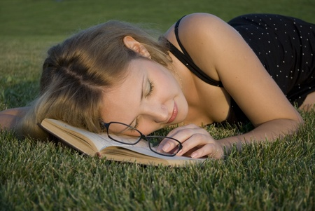 Young woman sleeping with book outdoors photo