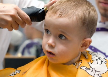 hairdressing scissors: Haircutting one and half year old boy in the hairdressing saloon Stock Photo